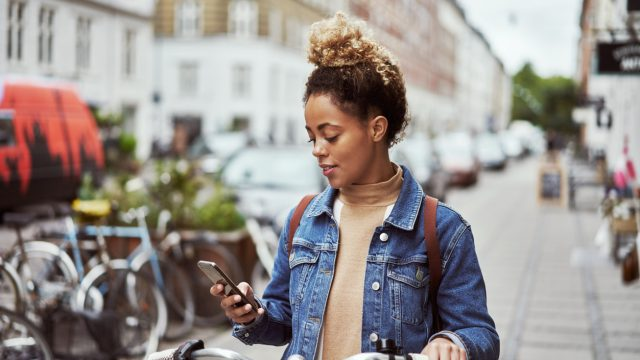 A young woman using her iPhone while riding a bike through the city