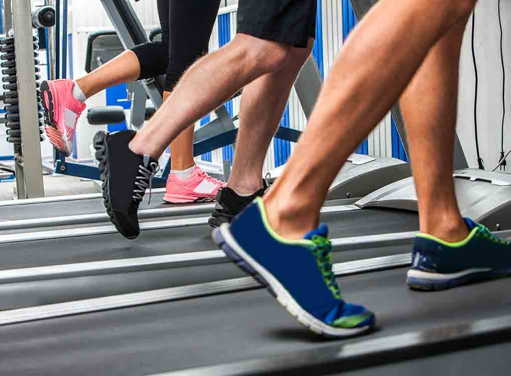 feet on a treadmill man and woman exercising cardio workouts for men over 40