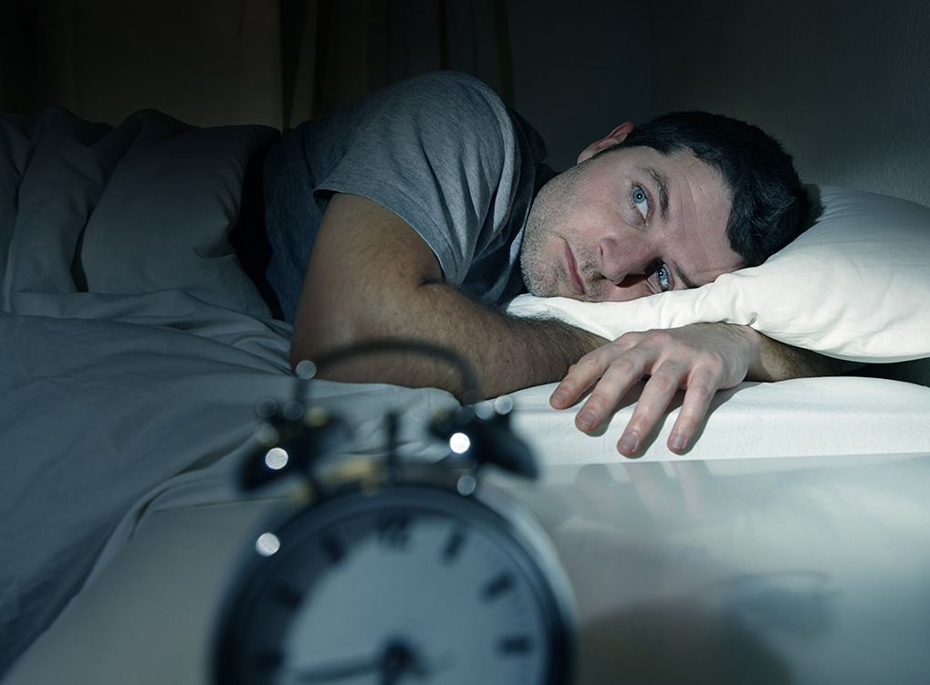 man in bed looking at alarm clock, ways your body changes after 40