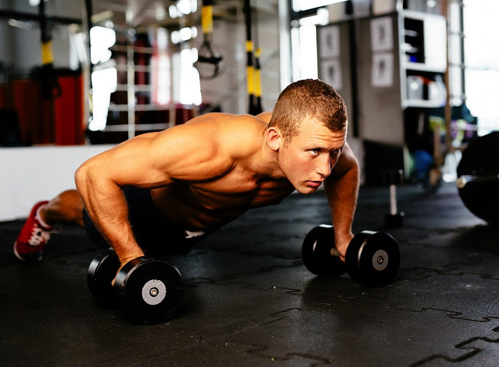man and woman exercising cardio workouts for men over 40 man with weights at the gym