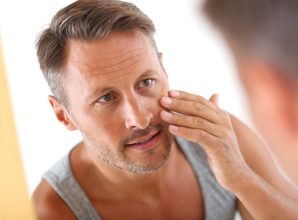 Man Applying Moisturizer Anti-Aging Tips You Should Forget