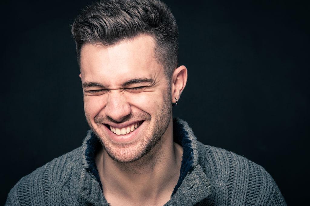 man laughing on black background bad jokes