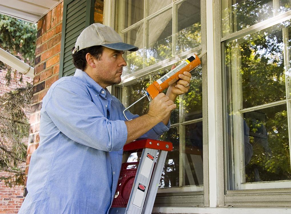 man caulking window