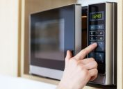 hand pressing button on microwave