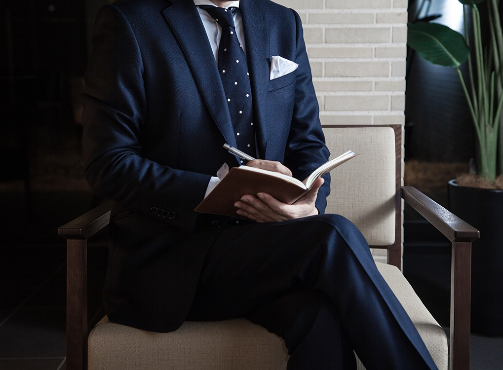 man in a suit reading a book - how to dress over 50