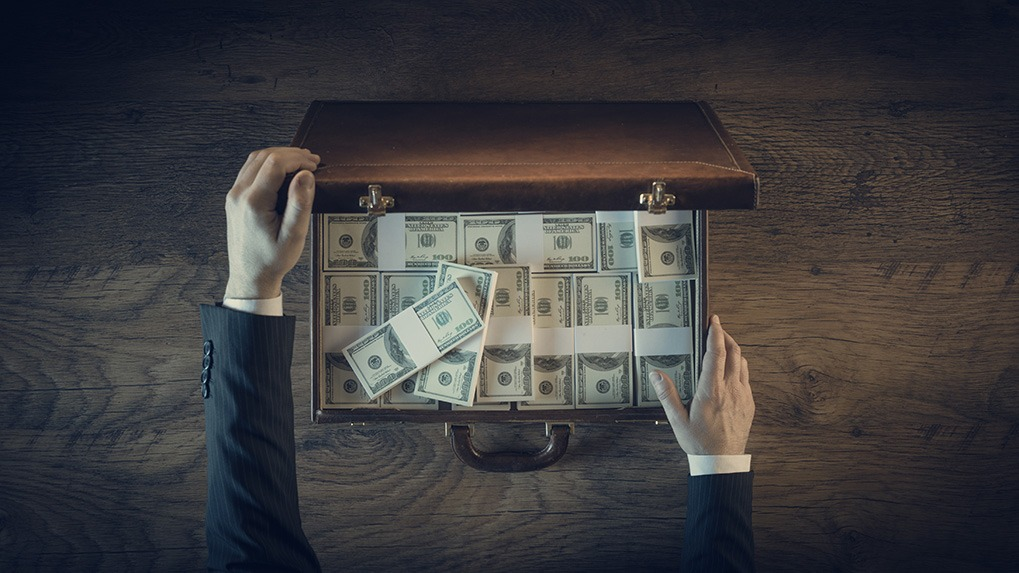 white man's hands opening briefcase full of cash