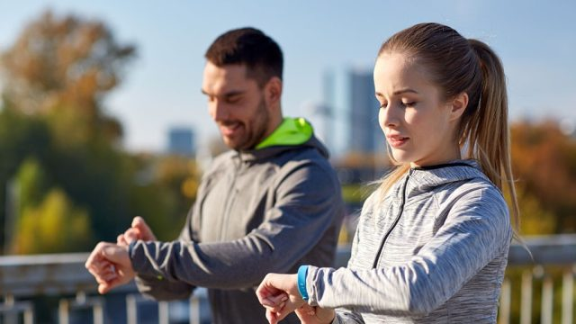 healthy man couple exercising checking smart watches fitbits