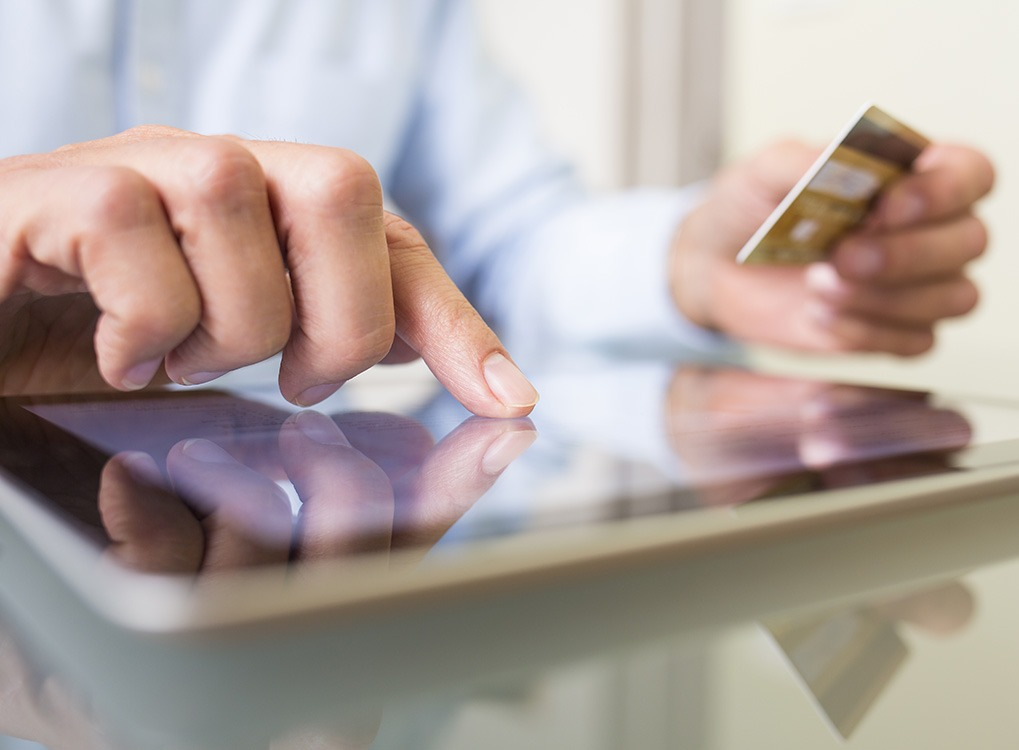 closeup of man's hand clicking on item on tablet while online shopping