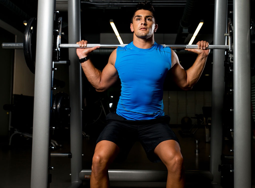 man lifting weights with a weight rack