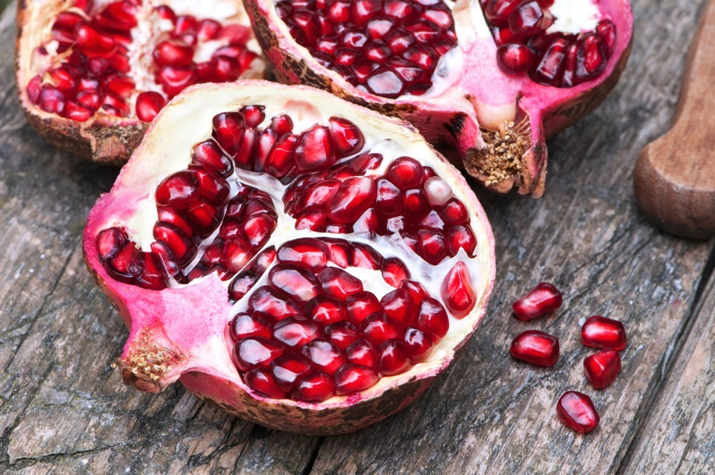 Cut pomegranates on wooden table